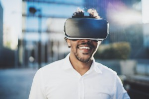 Concept of technology,gaming,entertainment and young people.Smiling american african man enjoying virtual reality glasses or 3d spectacles.Blurred background.Horizontal.